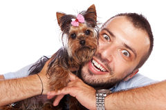 Young man holding a cute yorkie puppy dog Stock Image