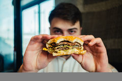Young man holding a delicious hamburhen and it is going to eat. Young man holding a tasty and hamburhen going to eat it. Focus is shown in full face food outlets Stock Photography