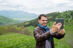 Young man holding digital tablet in front of him in nature Stock Photo