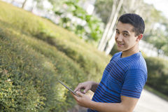 Young man holding digital tablet. Young man holding a digital talbet outdoors Royalty Free Stock Image