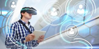 Composite image of young man holding digital tablet while using virtual reality simulator glasses. Young man holding digital tablet while using virtual reality Royalty Free Stock Photos