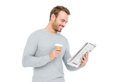 Young man holding disposable cup and reading newspaper. On white background Stock Photos