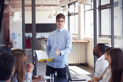 Young man holding document addressing colleagues at meeting Royalty Free Stock Photos
