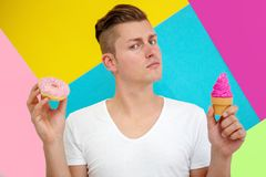 Young man holding a donut and icecream in front of colorful back stock photos