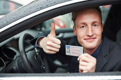 Young man holding drivers licence and thumps up Royalty Free Stock Photography