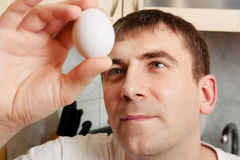 young man holding an egg Stock Images