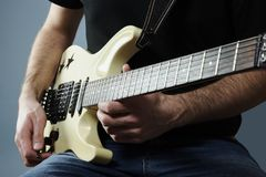 Young man holding a electric guitar. Hands of a young man holding a electric guitar Royalty Free Stock Images