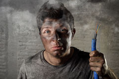 Young man holding electrical cable smoking after electrical accident with dirty burnt face in funny sad expression Royalty Free Stock Photo
