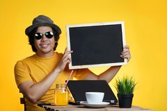 Young Man Holding Empty Blackboard While Working on Summer Vacat. Ion Season Against Yellow Background Stock Image