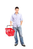 Young man holding an empty shopping basket. Full length portrait of a casual young man holding an empty shopping basket isolated on white background Stock Photos