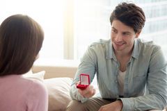 Young man holding engagement ring, making marriage proposal to g. Young guy holding box with engagement ring, making marriage proposal to girlfriend, requesting stock image