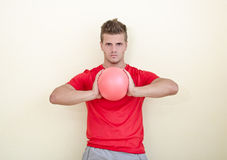 Young man holding exercise ball in his hands Royalty Free Stock Images