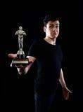Young man holding fake oscar award Stock Photos