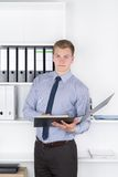Young man is holding a file in front of a shelf in the office Stock Image