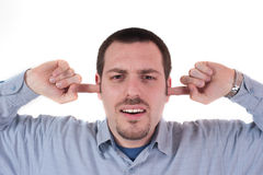 Young man holding fingers in ears, shutting them Stock Images