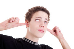 Young man, holding fingers in his ears, bored Royalty Free Stock Photos