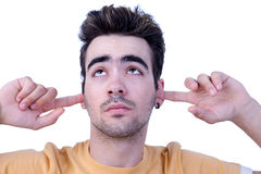 Young man, holding fingers in his ears, bored Royalty Free Stock Photo