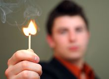 Young Man Holding Flaring Match. Young man holding a flaring wooden match toward the camera. Shallow DOF stock photos
