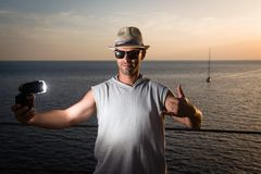Young man holding flash, sea view in background Royalty Free Stock Photography