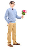 Young man holding flowers Royalty Free Stock Images