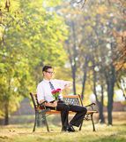 Young man holding flowers and checking the time Stock Photography