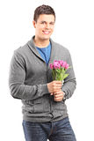 Young man holding flowers Stock Photography