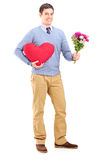 Young man holding flowers and red heart Royalty Free Stock Images