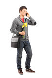 Young man holding flowers and talking on his phone Royalty Free Stock Photo