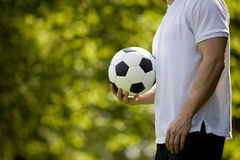 A young man holding a football, outdoors Royalty Free Stock Image