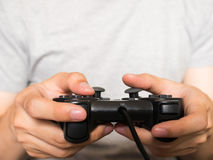 A young man holding game controller playing video games Royalty Free Stock Images