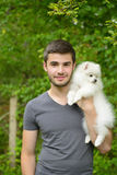 Young man holding german spitz puppy Royalty Free Stock Photo