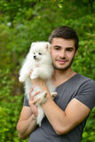 Young man holding german spitz puppy Stock Photo