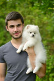 Young man holding german spitz puppy Royalty Free Stock Images