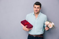 Young man holding gift box and flowers. Over gray background. Looking at camera Stock Image