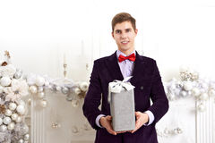 Young man holding gift box. With xmas decorations Royalty Free Stock Photos