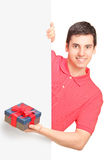 Young man holding a gift and standing behind panel Stock Photos