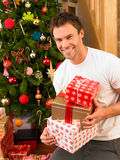 Young man holding gifts in front of Christmas tree Royalty Free Stock Photo