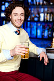 Young man holding a glass of beer Stock Image