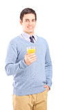 Young man holding a glass of orange juice Royalty Free Stock Image