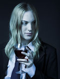 Young man holding glass of red vine. Portrait on black background Stock Photo