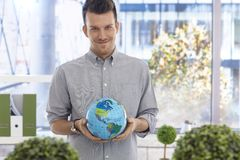 Young man holding globe smiling. Portrait of young man holding globe, smiling, looking at camera Stock Photography