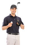 Young man holding a golf club and smiling Royalty Free Stock Images
