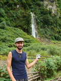 Young man holding GPS near waterfall in Nepal Royalty Free Stock Photos