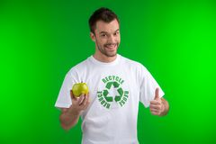 Young man holding green apple and doing thumbs up. Stock Photo