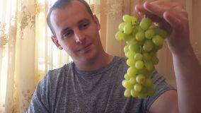 Young man holding green grapes in his hands stock footage