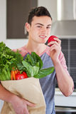 Young man holding groceries eating an apple Royalty Free Stock Image