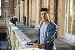 Young Man Holding a Guide Outside Historic Stock Photo