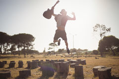 Young man holding guitar while jumping on tree stump Stock Image
