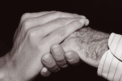 Young man holding the hand of an old man, in black and white Royalty Free Stock Image