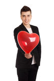 Young man holding heart shape balloon Royalty Free Stock Photos